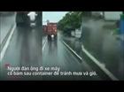 Xe máy tránh mưa sau xe container